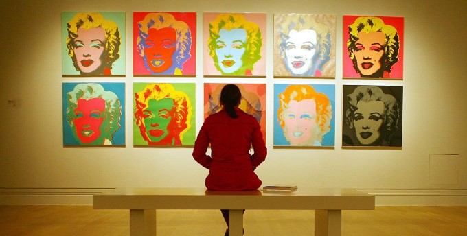 A visitor examines Andy Warhol's Marilyn Monroe 'Marilyn 1967' at the Pop Art Portraits exhibition, National Portrait Gallery in central London, 11 October 2007.  The exhibition brings together 52 key works from one of the world's most popular and influential art movements -- Pop Art.  'Pop Art Portraits' contains works from 28 artists from Britain and the United States, including Andy Warhol, Roy Lichtenstein and David Hockney, and is designed to show how the genre evolved and revolutionised portrait painting. It examines how the artists depicted the famous and their use of images drawn from advertising, pop music, the cinema, magazines and newspapers.  (Photo credit should read BEN STENSALL/AFP/Getty Images)