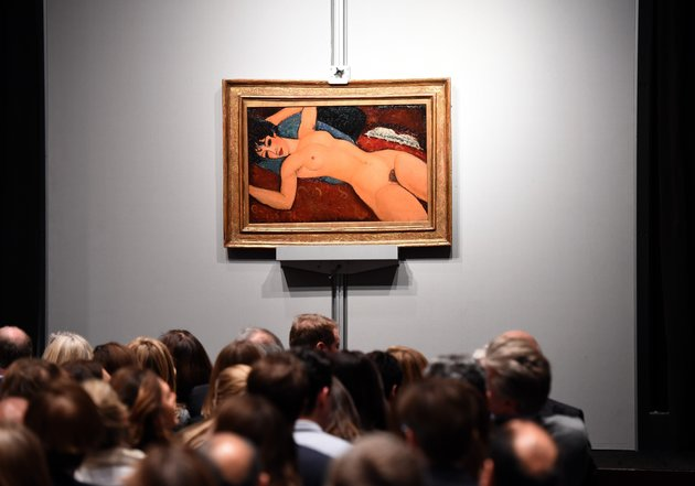 "Crowds sit in front of Amedeo Modigliani's ""Nu couche"" during the ""Artist Muse: A Curated Evening Sale"" November 9, 2015 at Christie's New York  November 9, 2015.  The painting sold for USD170,405,000. AFP PHOTO / TIMOTHY A. CLARY        (Photo credit should read TIMOTHY A. CLARY/AFP/Getty Images)"