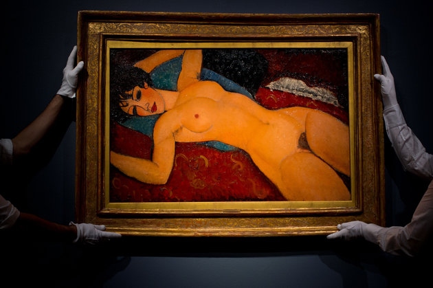 LONDON, ENGLAND - OCTOBER 09:  Art handlers hang the painting 'Nu couche' by artist Amedeo Modigliani during the preview ahead of the artist's muse: a curated evening sale in Christie's New York on October 9, 2015 in London, England. The impressionist, modern, post-war and contemporary works will be on show to the public between October 10 and October 17 and includes Amedeo Modigliani's 'Nu couche' which is estimated to sell for 100 USD million. The sale also showcases pieces by artists including Lucian Freud, Paul Cezanne, Peter Doig, Pablo Picasso, Alberto Giacometti, Amedeo Modigliani and Roy Lichtenstein.  (Photo by Ben Pruchnie/Getty Images)