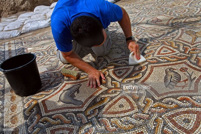 LOD, ISRAEL - JULY 01: A worker cleans the dirt off an ancient Roman mosaic as it is revealed some 13 years after it was first discovered in the ruins of a 4th century AD building, on July 1, 2009 in Lod in central Israel. The beautiful 1,700 year old mosaic floor, which is regarded as one of the most magnificent and largest ever revealed in Israel, was first uncovered in 1996 during a project to upgrade the city's sewage system. The well-preserved mosaic covers an area of about 180 square meters and is composed of coloured carpets that depict in detail animals, birds, fish, a variety of flora and the sailing and merchant ships that were used at the time. (Photo by David Silverman/Getty Images)
