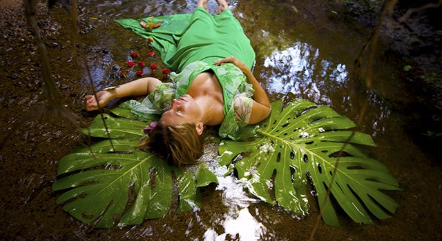 A fallen angel lay in her reflection. Behind her rest her large green wings, in the water there is a reflection of the sky.