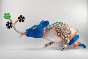 Artist creating three-dimensional sculptures using traditional piñata motifs.